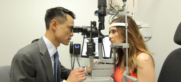 Dr. Gee examines the eyes of one of his patients at his private practice in Houston